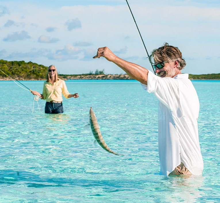 Man and woman holding Fishing Poles with a bone fish