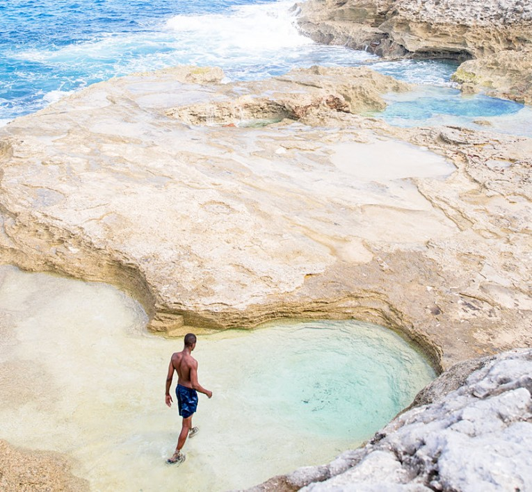 Man walking in Queen's Bath rocks in Eleuthera Bahamas