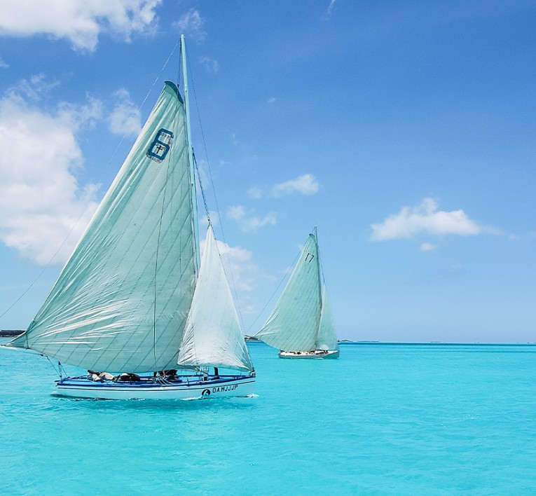 two sloop sail boats cruising on Bahamian water