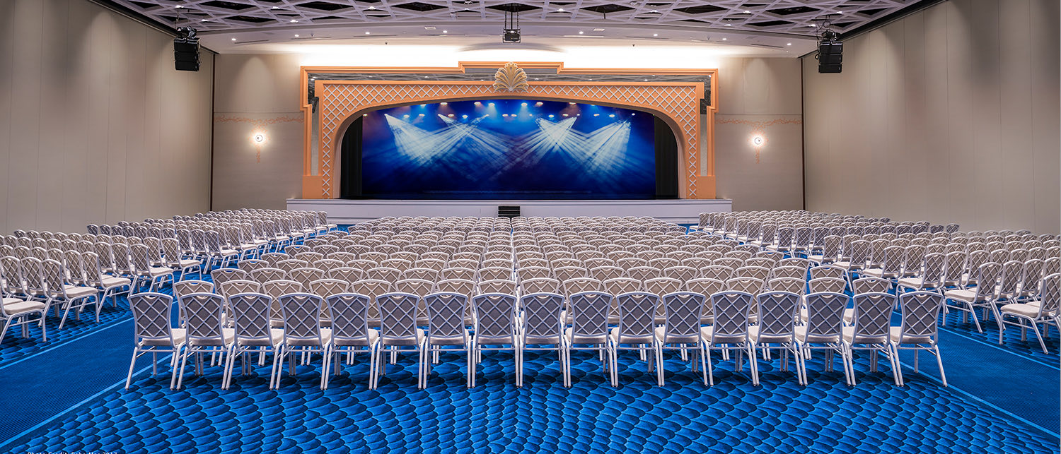 Large Event room with blue carpet, chairs and large stage at the center