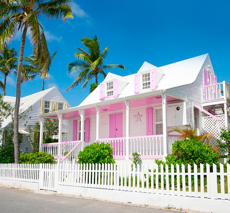 bright prink house with white trimmings and white picket fence