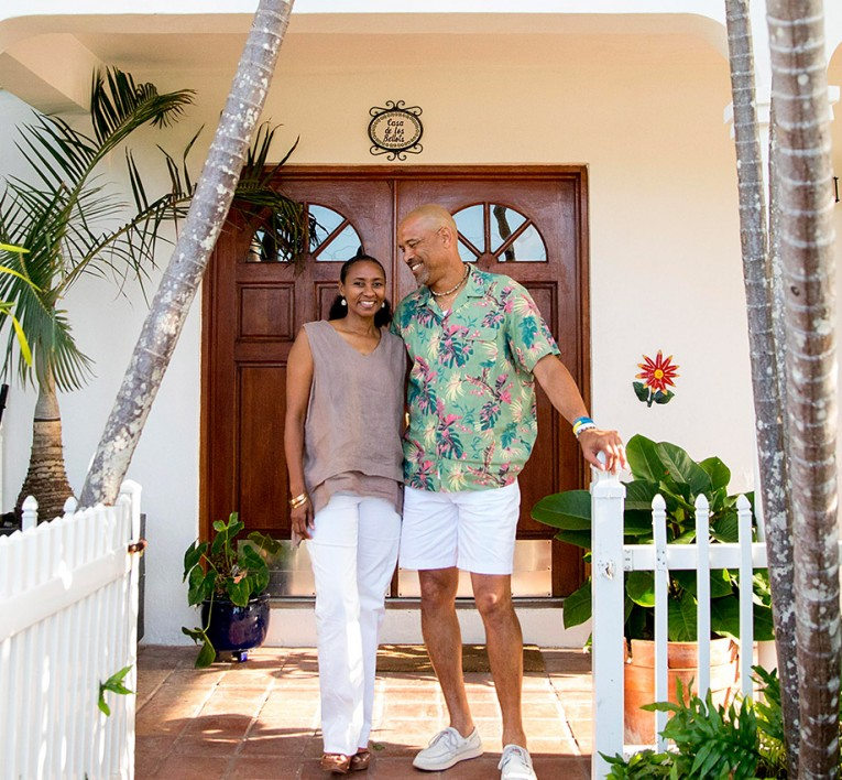a couple standing in a tropical front porch